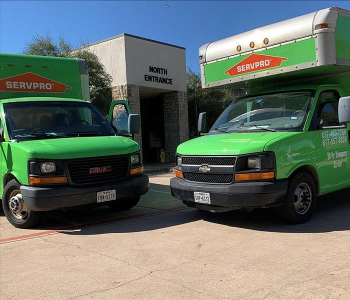 Two servpro trucks are parked outside a commercial facility